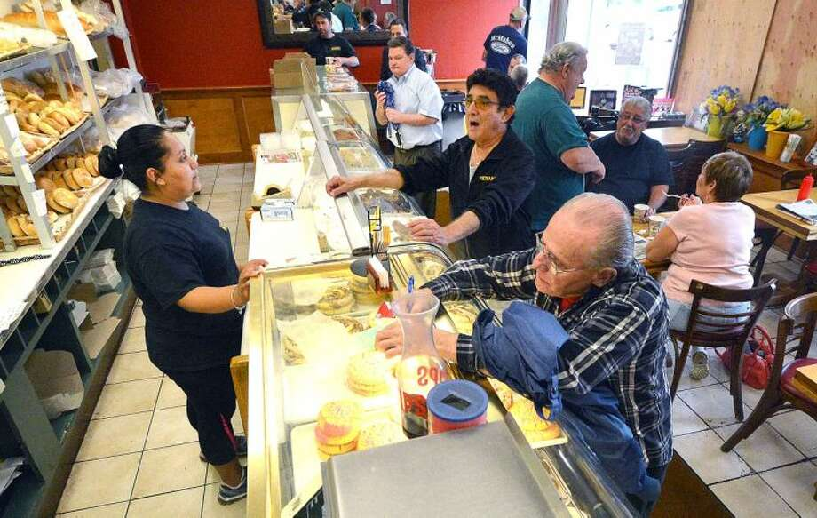 Hour Photo/Alex von Kleydorff Ruth Velazquez keeps the customers moving along the bakery counter at Muro's on Wednesday