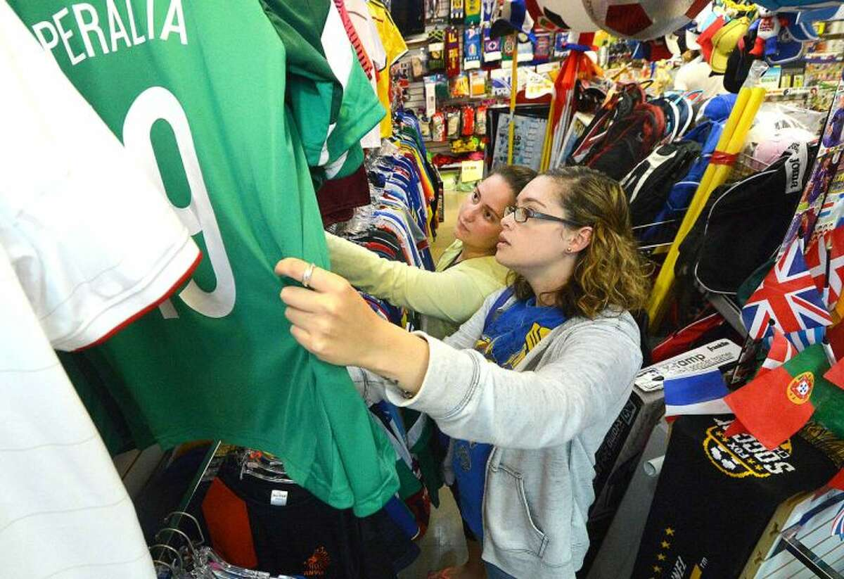 Hour Photo/Alex von Kleydorff Valeska Diaz and Rosa Chiappetta shop through hundreds of soccer jerseys looking for the perfect Fathers Day gift for thier dads, fans of the Mexican and Columbian teams in The Word Cup