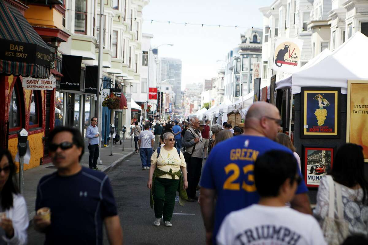 Festival goers walk by booths at the 62nd North Beach Festival on Saturday, June 11, 2016 in San Francisco, California. The festival includes loud music, venters, art and other food.