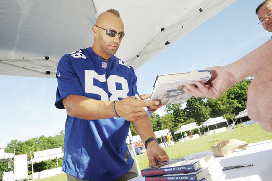Mark Herzlich, a linebacker for the New York Giants and a Bone Cancer Survivor signs his book What it Takes: Fighting for my Life and My Love for the Game at the 5K Race for Multiple Myleoma at New Canaan High School on Sunday. Hour photo/Matthew Vinci