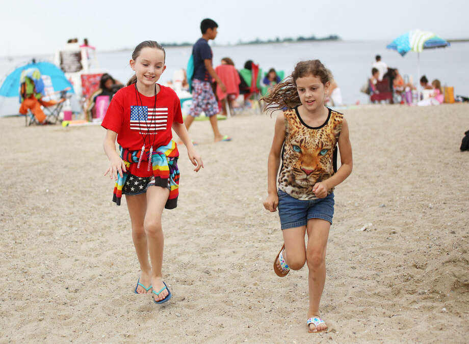 Julia Dennehy, 9, and Emilu Koba, 9, play in the sand before Norwalk's annual firework display at Calf Pasture Beach in Norwalk Friday evening. Hour Photo / Danielle Calloway