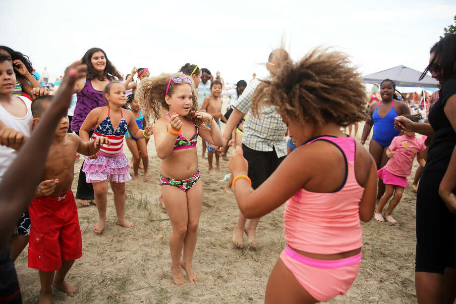 Jailene Diaz, 8, dances to music played by DJ Jim Nuzzo before Norwalk's annual firework display at Shady Beach in Norwalk Friday evening. Hour Photo / Danielle Calloway