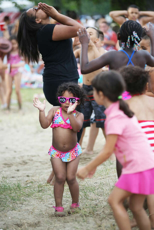 Camila Mercado, 2, dances to music played by DJ Jim Nuzzo before Norwalk's annual firework display at Shady Beach in Norwalk Friday evening. Hour Photo / Danielle Calloway
