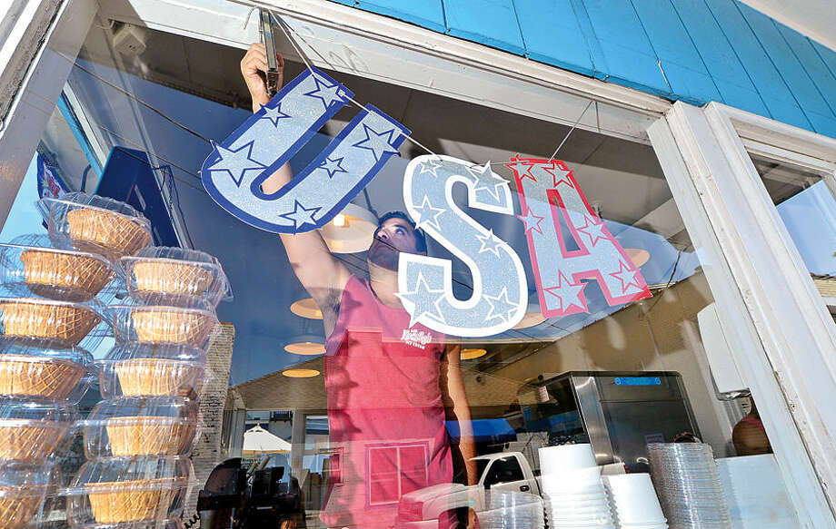 Hour photo / Erik Trautmann Owner of Mr. Frostys Ice Cream on Seaview Ave, Anthony Luciani, puts up Independance Day decorations for the holiday weekend Friday.