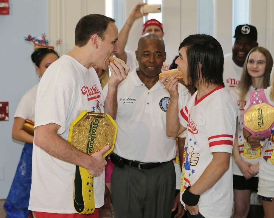 Brooklyn Borough President Eric Adams watches Joey Chestnut, left, and Matt Stonie, right, during a news conference to promote the upcoming Nathan's Famous Fourth of July Hot-Dog Eating Contest Friday, July 3, 2015, at Brooklyn Borough Hall in New York. (AP Photo/Frank Franklin II)