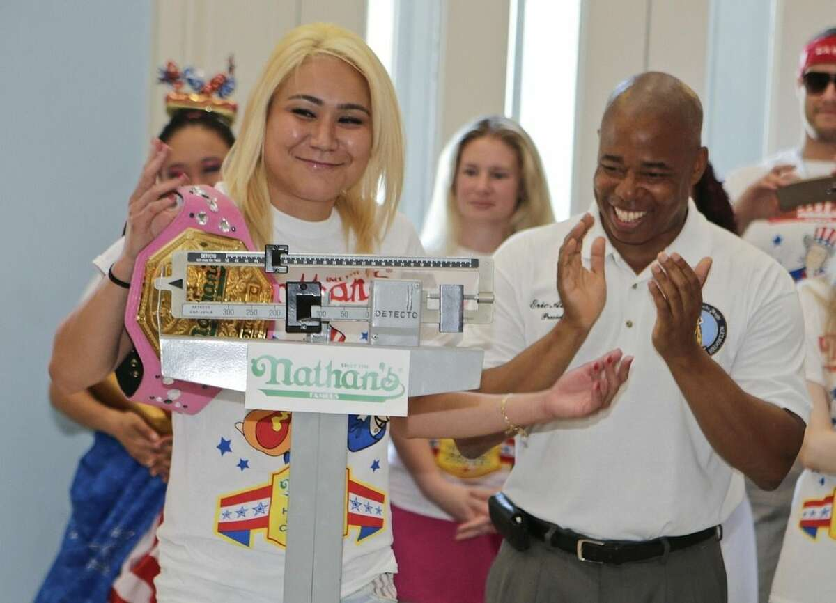 Brooklyn Borough President Eric Adams, claps for Miki Sudo, left, during a news conference to promote the upcoming Nathan's Famous Fourth of July Hot-Dog Eating Contest Friday, July 3, 2015, at Brooklyn Borough Hall in New York. The contest is Saturday, July 4. (AP Photo/Frank Franklin II)