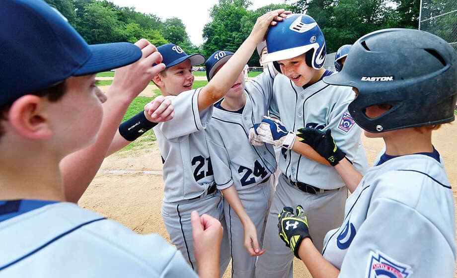 Hour photo / Erik Trautmann Wilton's Patrick Cummins in congratulated by his teammates after hitting a solo home run during their District 1 Little League game against Darien National at McGuane Field in Noroton Heights Saturday.