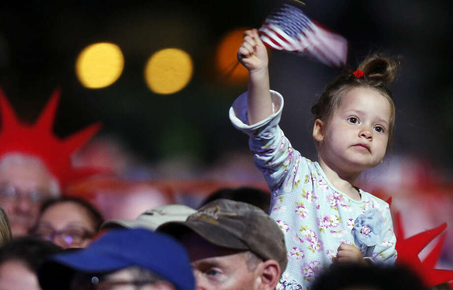 A young girl waves a flag during rehearsal for the annual Boston Pops orchestra Fourth of July concert at the Hatch Shell in Boston, Friday, July 3, 2015. (AP Photo/Michael Dwyer)