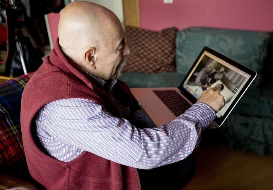 In this June 19, 2015 photo, Dr. Gustavo Quintana, who helps people with terminal illnesses end their lives, points to a video that shows him with a patient, as he speaks during an interview in Bogota, Colombia. Quintana says barely a week goes by without him receiving a phone call from a desperate patient or family member looking to end their agony. He claims to have helped more sick people die than the late Jack Kevorkian. (AP Photo/Fernando Vergara)