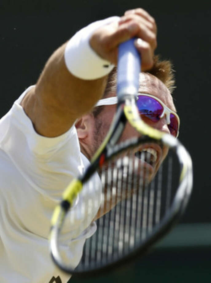 Viktor Troicki of Serbia returns the ball to Dustin Brown of Germany during the singles tennis match at the All England Lawn Tennis Championships in Wimbledon, London, Saturday July 4, 2015. (AP Photo/Pavel Golovkin)