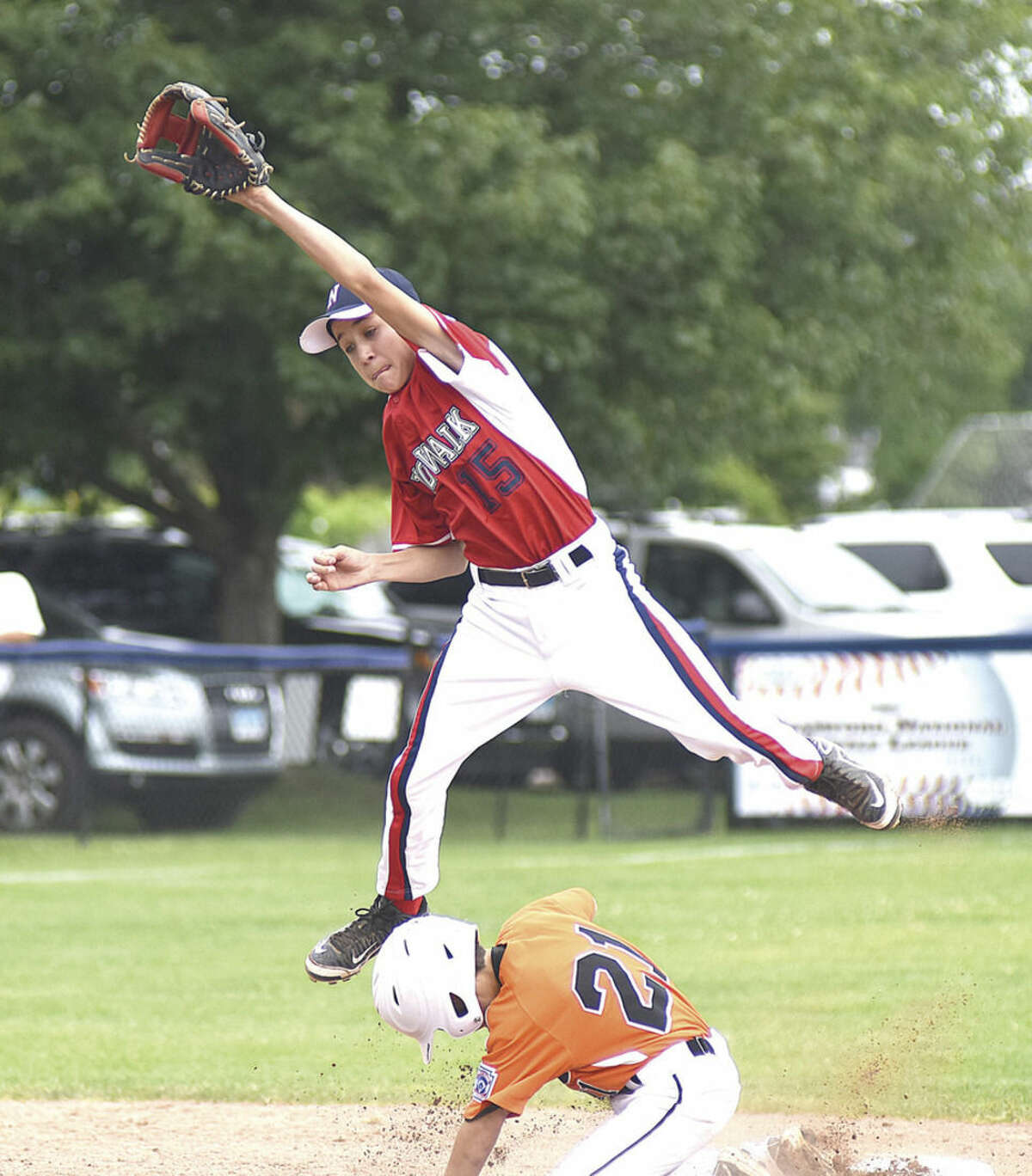Hour photo/John Nash Norwalk shortstop Korey Morton, top, extends high for a throw as Ridgefield's Alex Hanna slides safely into second base on a double during Saturday's District 1 12-year-old tournament game in Stamford.