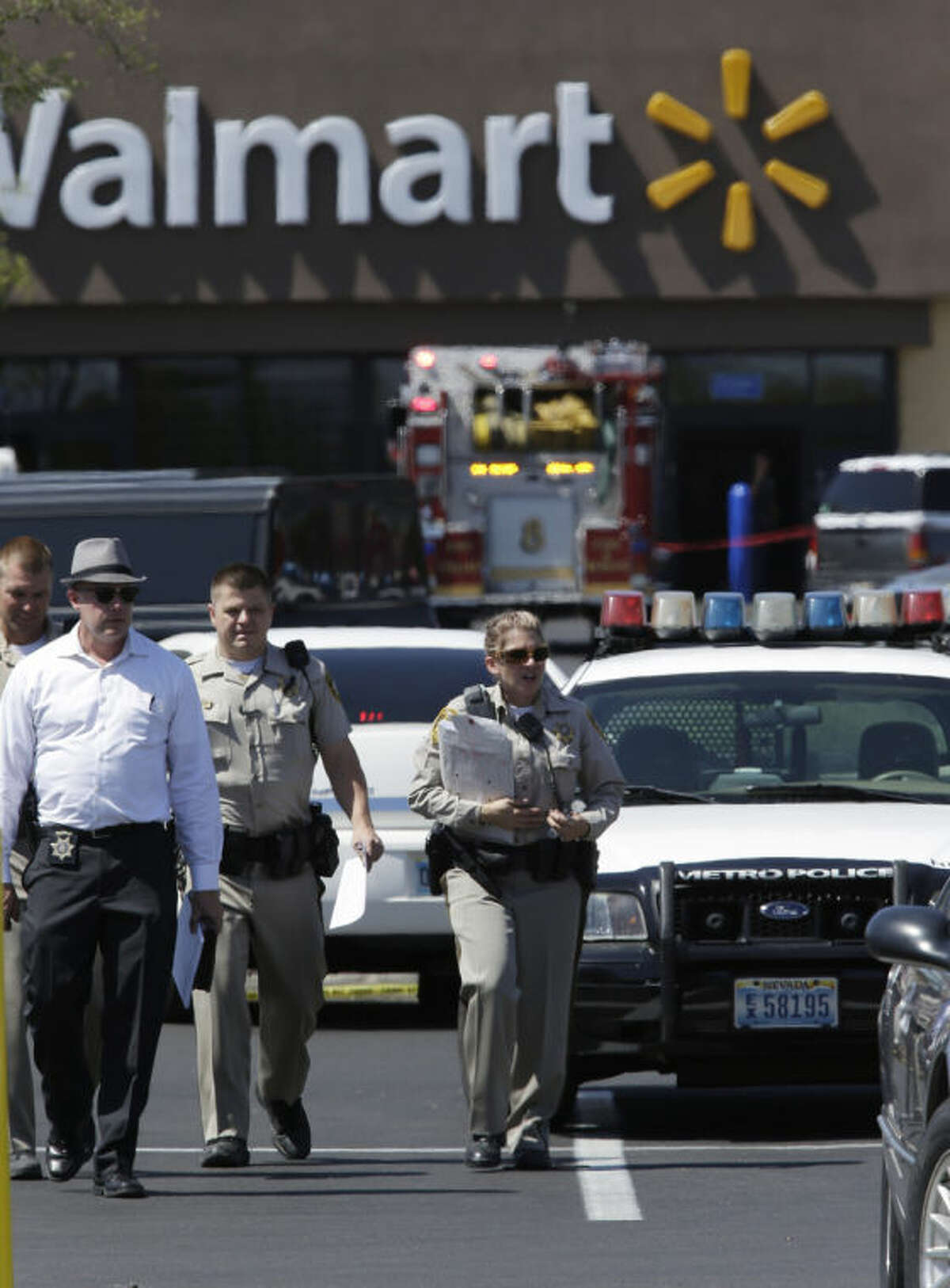 Las Vegas Metropolitan Police Department officers are at the scene of a shooting Sunday, June 8, 2014 in Las Vegas. Police say two suspects shot two officers at a Las Vegas pizza parlor before fatally shooting a person and turning the guns on themselves at a nearby Walmart. (AP Photo/John Locher)