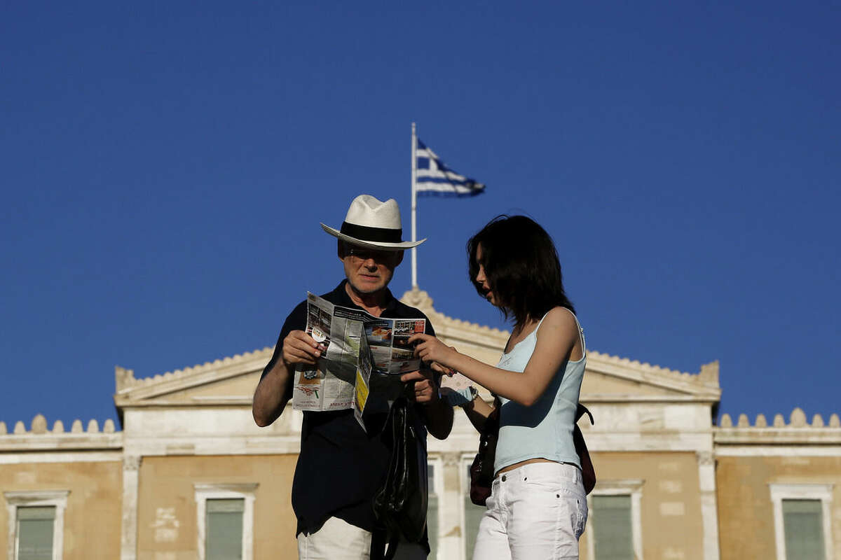Tourists look at a map as they stand at Syntagma square in front of the parliament in central Athens, on Saturday, July 4, 2015. Whether Greeks decide in Sunday's referendum to accept their lenders' bailout deal or reject it, the government's hold on power may be shakier than its brash prime minister has calculated, analysts say. (AP Photo/Petros Karadjias)