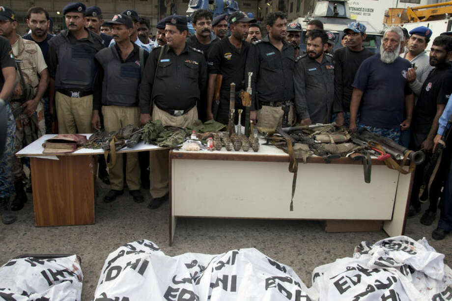 Pakistani police officers display confiscated ammunition and the dead bodies of terrorists who attacked the Jinnah International Airport Monday, June 9, 2014, in Karachi, Pakistan. Gunmen disguised as police guards attacked a terminal at Pakistan's busiest airport with machine guns and a rocket launcher during a five-hour siege that killed over a dozen people as explosions echoed into the night, while security forces retaliated and killed all the attackers, officials said Monday. (AP Photo/Shakil Adil)