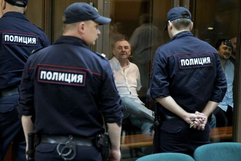 Lom-Ali Gaitukayev, background center, and Rustam Makhmudov, right, accused of the murder of journalist Anna Politkovskaya, await the judge's verdict in a glass cage, at the Moscow City Court, in Moscow, Russia, Monday, June 9, 2014. The Moscow City Court has sentenced two men to life in prison and three others to terms ranging from 12 to 20 years for the 2006 killing of renowned journalist Anna Politkovskaya. Politkovskaya, 48, was noted for her reporting that criticized Kremlin policies in Chechnya and human rights violations there. She was shot to death in the elevator of her Moscow apartment building. (AP Photo/Pavel Golovkin)