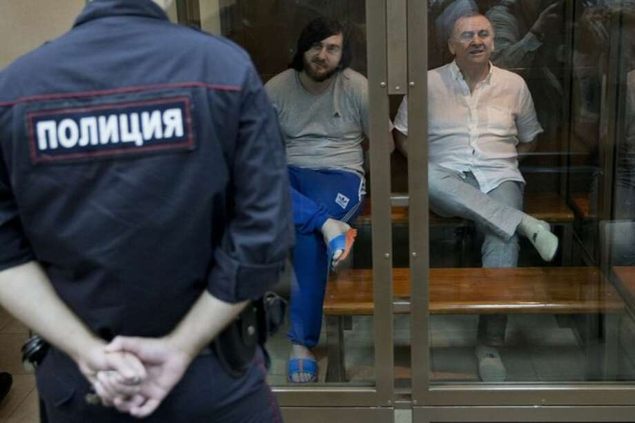 Ibragim Makhmudov, center, and Lom-Ali Gaitukayev, right, accused of the murder of journalist Anna Politkovskaya, await the judge's verdict in a glass cage, at the Moscow City Court, in Moscow, Russia, Monday, June 9, 2014. The Moscow City Court has sentenced two men to life in prison and three others to terms ranging from 12 to 20 years for the 2006 killing of renowned journalist Anna Politkovskaya. Politkovskaya, 48, was noted for her reporting that criticized Kremlin policies in Chechnya and human rights violations there. She was shot to death in the elevator of her Moscow apartment building. (AP Photo/Pavel Golovkin)