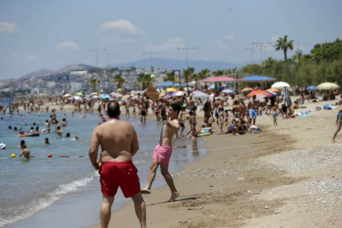 Bathers play rackets on the beach during Greece's referendum day in southern Athens, Sunday, July 5, 2015. Greeks were voting Sunday in a bailout referendum that will decide the country's future, with opinion polls showing people evenly split on whether to accept creditors' proposals for more austerity in exchange for rescue loans or defiantly reject the deal. (AP Photo/Petr David Josek)