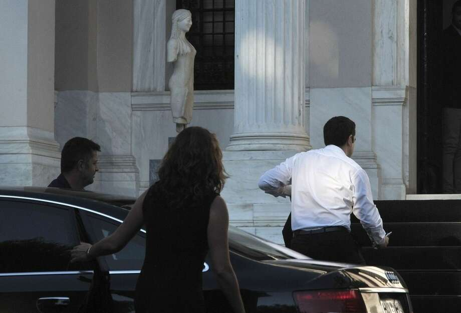 "Greece's Prime Minister Alexis Tsipras, right, arrives with his partner Peristera (Betty) Baziana at Maximos Mansion in Athens, Sunday, July 5, 2015. Three opinion polls carried out during Greece's bailout referendum, which could affect the country's future in the eurozone, indicate the ""no"" vote will win. Tsipras called Sunday's referendum last weekend, urging voters to reject creditor reform proposals. (AP Photo/Angelos Christofilopoulos)"