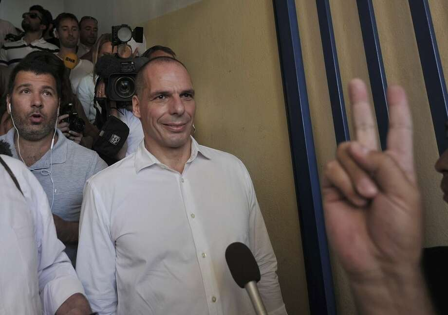 Greece's Finance Minister Yanis Varoufakis leaves after voting as a supporter makes the victory sign at a polling station in Athens, Sunday, July 5, 2015. Greeks were voting Sunday in a bailout referendum that will decide the country's future, with opinion polls showing people evenly split on whether to accept creditors' proposals for more austerity in exchange for rescue loans or defiantly reject the deal. (AP Photo/Angelos Christofilopoulos)
