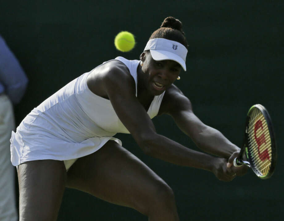 Venus Williams of the United States returns a ball to Aleksandra Krunic of Serbia during their singles match at the All England Lawn Tennis Championships in Wimbledon, London, Friday July 3, 2015. (AP Photo/Tim Ireland)