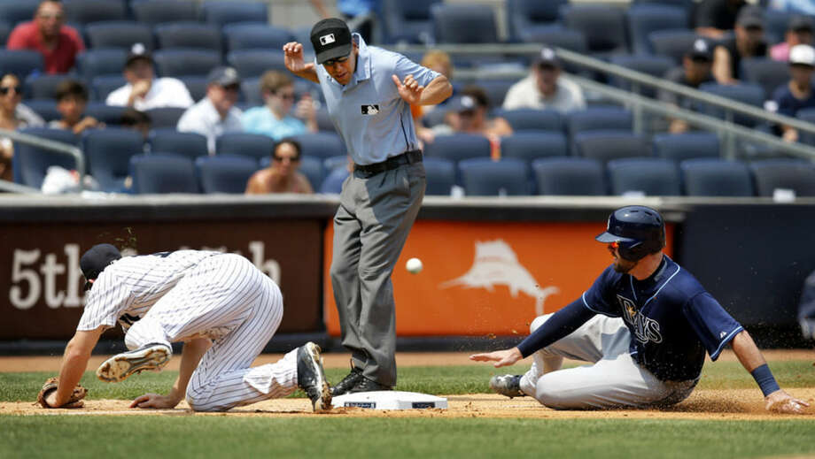 New York Yankees' Ivan Nova's errant throw skips away from Yankees third baseman Chase Headley, left, as Tampa Bay Rays' Curt Casali, right, and umpire Gabe Morales, center, react in the fifth inning of a baseball game at Yankee Stadium in New York, Sunday, July 5, 2015. Casali scored on the error. (AP Photo/Kathy Willens)