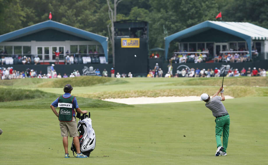Scott Langley, right, takes his second shot to the 17th green during the final round of the Greenbrier Classic golf tournament at Greenbrier Resort in White Sulphur Springs, W.Va., Sunday, July 5, 2015. Langley finished at 10-under-par for the four rounds. (AP Photo/Steve Helber)