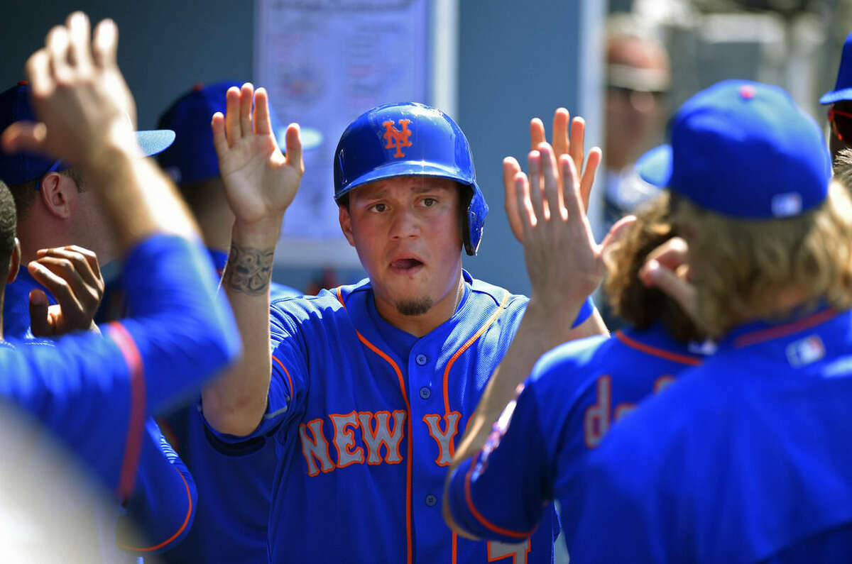 New York Mets' Wilmer Flores is congratulated by teammates after scoring on a single by Ruben Tejada during the seventh inning of a baseball game against the Los Angeles Dodgers, Sunday, July 5, 2015, in Los Angeles. (AP Photo/Mark J. Terrill)