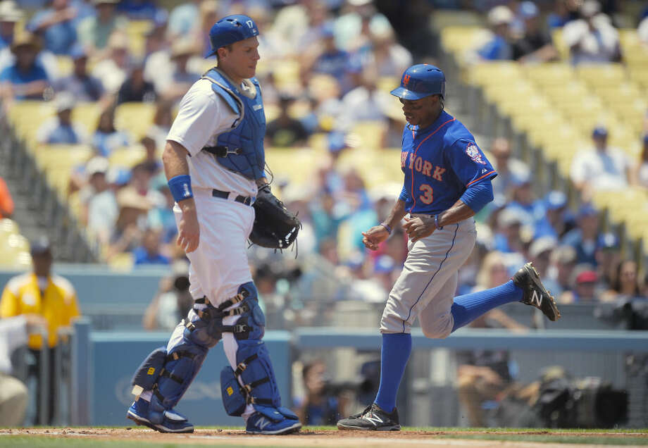 New York Mets' Curtis Granderson, right, scores on a single by Wilmer Flores as Los Angeles Dodgers catcher A.J. Ellis watches during the first inning of a baseball game, Sunday, July 5, 2015, in Los Angeles. (AP Photo/Mark J. Terrill)