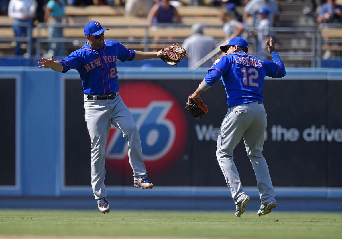 New York Mets' Michael Cuddyer, left, and Juan Lagares celebrate after they defeated the Los Angeles Dodgers 8-0 in a baseball game, Sunday, July 5, 2015, in Los Angeles. (AP Photo/Mark J. Terrill)