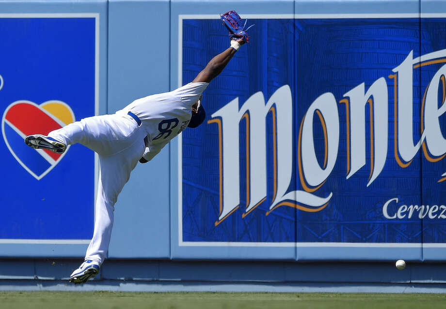 Los Angeles Dodgers right fielder Yasiel Puig misplays a ball hit for a triple by New York Mets' Juan Lagares during the seventh inning of a baseball game, Sunday, July 5, 2015, in Los Angeles. (AP Photo/Mark J. Terrill)