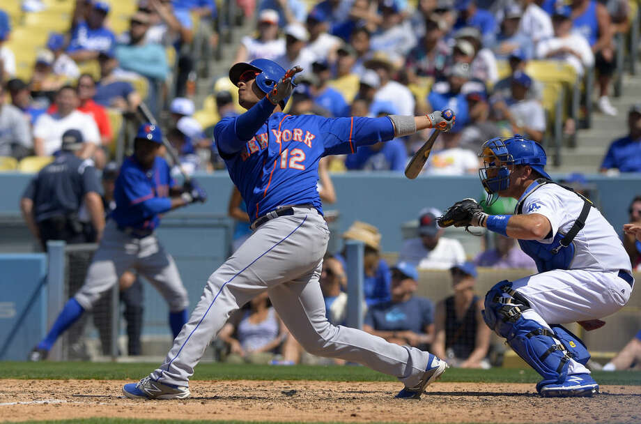 New York Mets' Juan Lagares, left, hits an RBI-triple as Los Angeles Dodgers catcher A.J. Ellis, right, watches during the seventh inning of a baseball game, Sunday, July 5, 2015, in Los Angeles. (AP Photo/Mark J. Terrill)