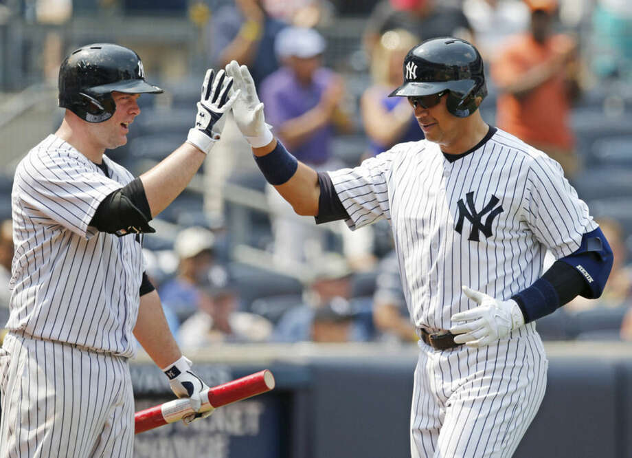 New York Yankees on-deck batter Brian McCann, left, greets New York Yankees designated hitter Alex Rodriguez after Rodriguez hit a sixth-inning solo home run in the Yankees 8-1 loss to the Tampa Bay Rays in a baseball game at Yankee Stadium in New York, Sunday, July 5, 2015. (AP Photo/Kathy Willens)