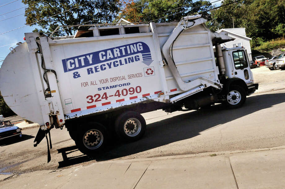 Hour photo / Matthew VinciA City Carting & Recycling truck moves through South Norwalk Monday. It is the first day of a 10-year contract the company has with the city.