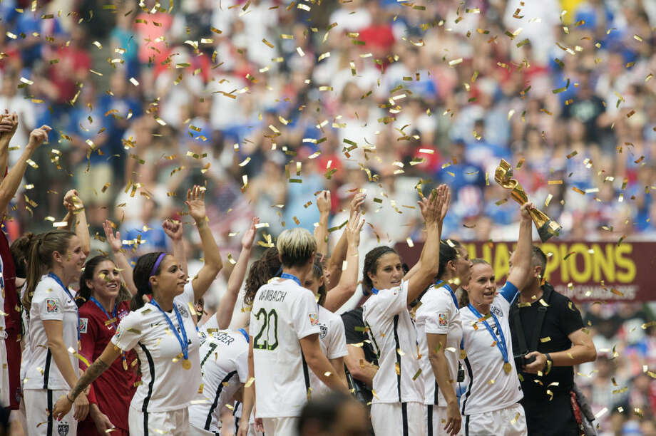 Christie Rampone, right, lifts the trophy as USA teammates celebrate following their win over Japan in the FIFA Women's World Cup soccer championship in Vancouver, British Columbia, Canada, Sunday, July 5, 2015. (Jonathan Hayward/The Canadian Press via AP) MANDATORY CREDIT