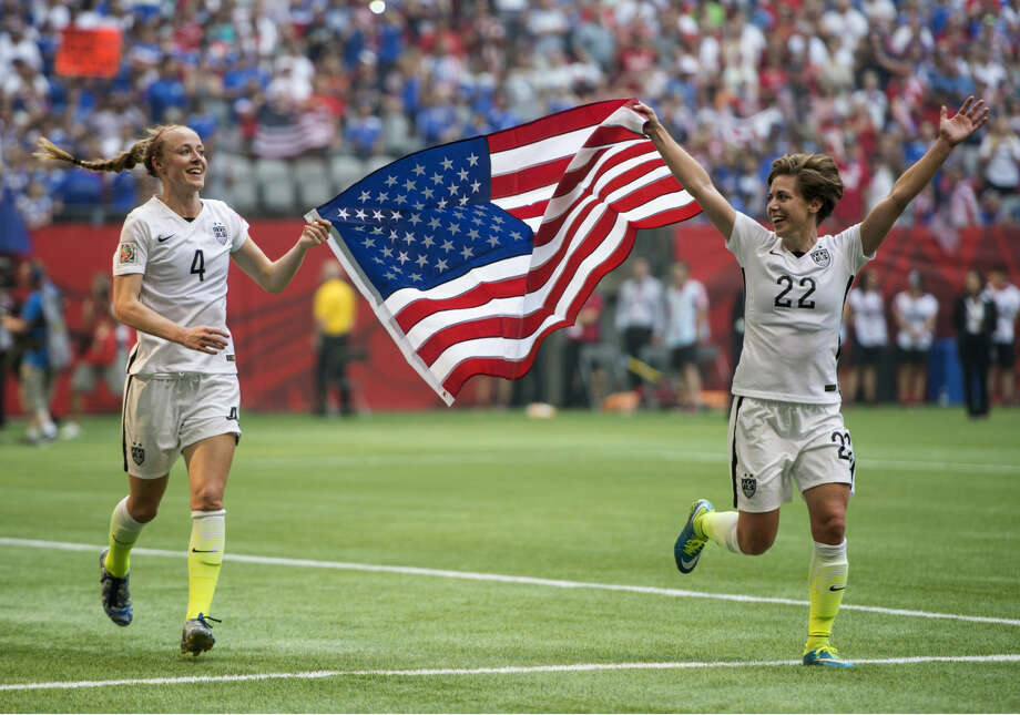 USA teammates Becky Sauerbrunn, left, and Meghan Klingenberg celebrate following their win over Japan at the FIFA Women's World Cup soccer championship in Vancouver, British Columbia, Canada, Sunday, July 5, 2015. (Jonathan Hayward/The Canadian Press via AP) MANDATORY CREDIT