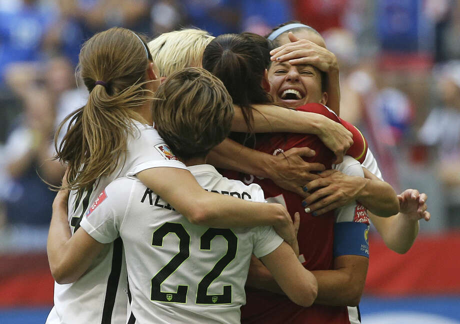 United States' Carli Lloyd, right, celebrates with teammates after Lloyd scored her third goal against Japan during the first half of the FIFA Women's World Cup soccer championship in Vancouver, British Columbia, Canada, Sunday, July 5, 2015. (AP Photo/Elaine Thompson)