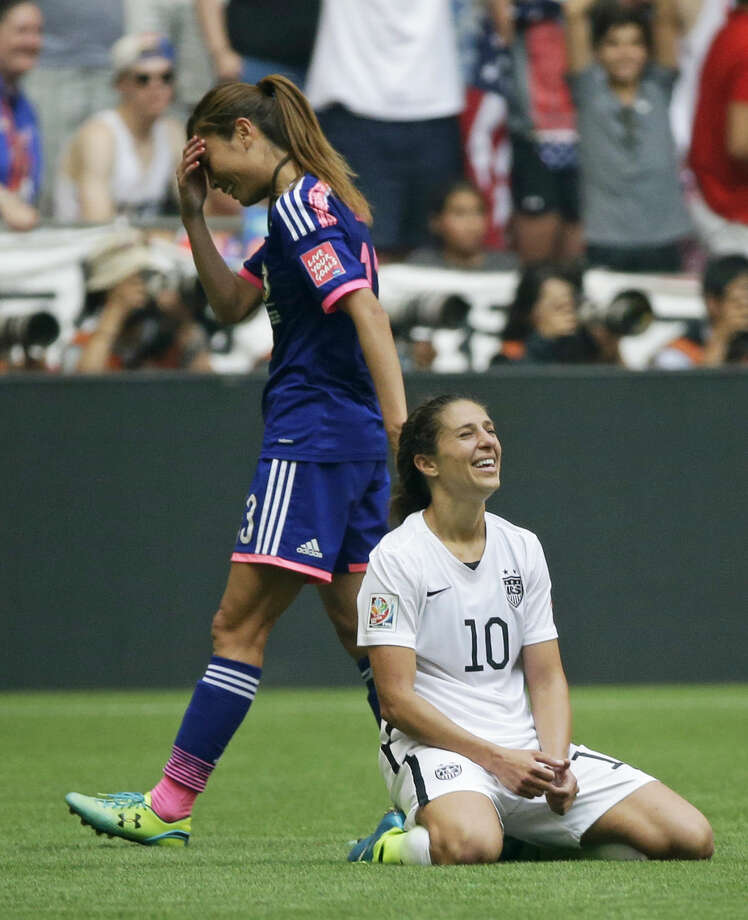 United States' Carli Lloyd kneels on the pitch as Japan's Rumi Utsugi, left, walks off after the U.S. beat Japan 5-2 in the FIFA Women's World Cup soccer championship in Vancouver, British Columbia, Canada, Sunday, July 5, 2015. (AP Photo/Elaine Thompson)