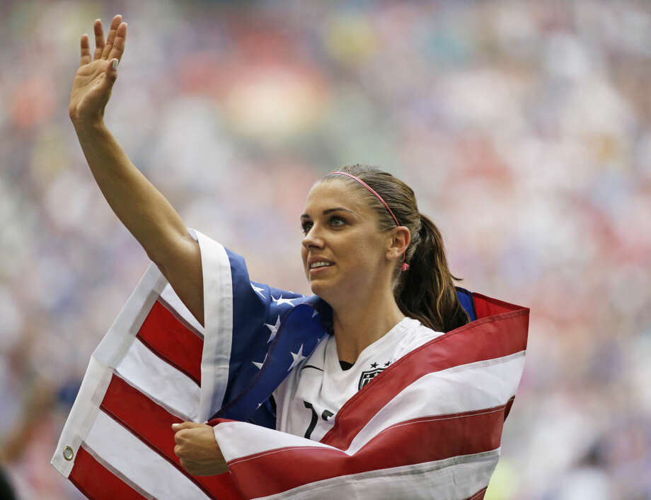 United States' Alex Morgan is draped in the U.S. flag as she waves to fans after the U.S. beat Japan 5-2 in the FIFA Women's World Cup soccer championship in Vancouver, British Columbia, Canada, Sunday, July 5, 2015. (AP Photo/Elaine Thompson)