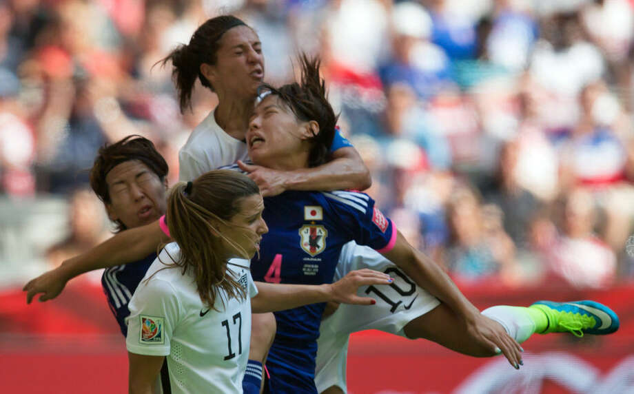 United States' Carli Lloyd, top, collides with Japan's Saki Kumagai (4) during the first half of the FIFA Women's World Cup soccer championship in Vancouver, British Columbia, Canada, on Sunday, July 5, 2015. (Darryl Dyck/The Canadian Press via AP) MANDATORY CREDIT
