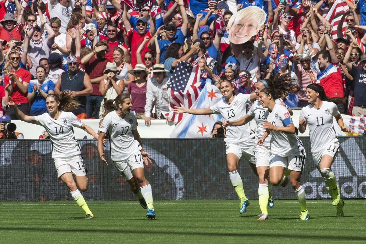 United States teammates, from left to right, Morgan Brian (14), Tobin Heath (17), Alex Morgan (13), Lauren Holiday (12), Carli Lloyd (10) and Ali Krieger (11) celebrate after Lloyd's second goal against Japan during the first half of the FIFA Women's World Cup soccer championship in Vancouver, British Columbia, Canada, on Sunday, July 5, 2015. (Jonathan Hayward/The Canadian Press via AP) MANDATORY CREDIT
