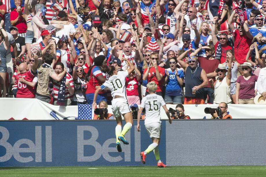United States' Carli Lloyd (10) and Megan Rapinoe celebrate Lloyd's goal against Japan during first half action in the FIFA Women's World Cup soccer championship in Vancouver, British Columbia, Canada, Sunday, July 5, 2015. (Jonathan Hayward/The Canadian Press via AP) MANDATORY CREDIT