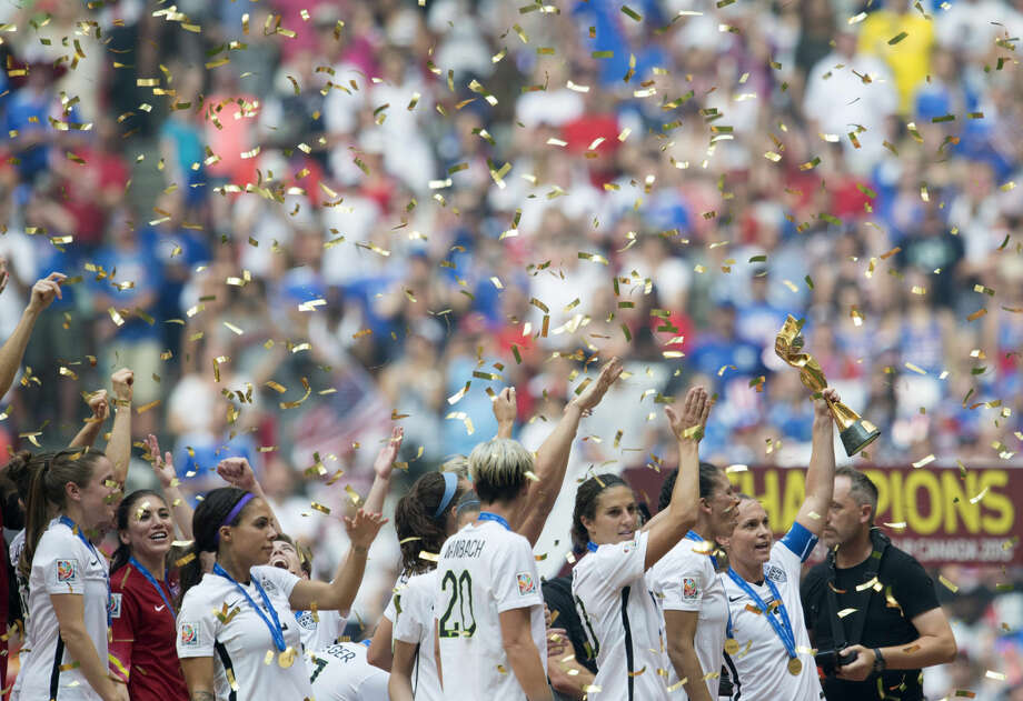 USA team members celebrate as Christie Rampone lifts the trophy following their win over Japan at the FIFA Women's World Cup soccer championship in Vancouver, British Columbia, Canada, Sunday, July 5, 2015. (Jonathan Hayward/The Canadian Press via AP) MANDATORY CREDIT