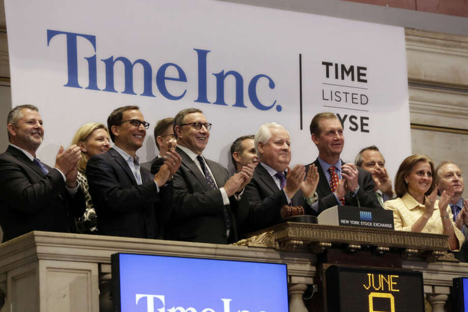Time Inc. Chairman and CEO Joseph Ripp, center, joins the applause as he rings the New York Stock Exchange opening bell to mark his company first day of trading as a stand-alone public company, Monday, June 9, 2014. (AP Photo/Richard Drew)