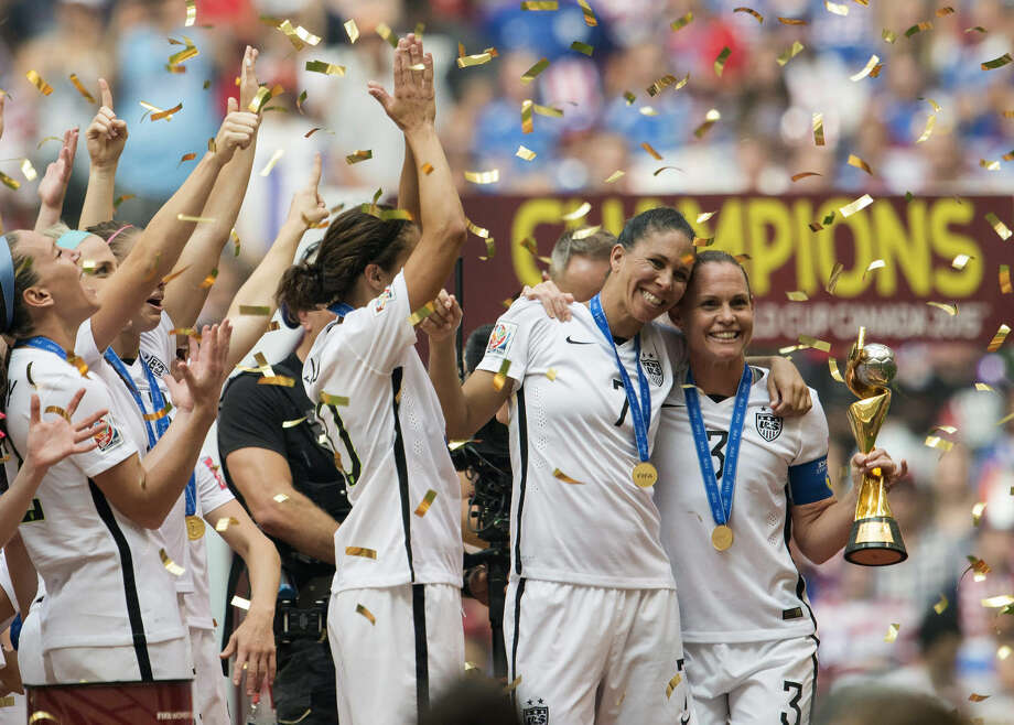 USA teammates Shannon Boxx, second from right, and Christie Rampone, far right, pose with the trophy as the USA team celebrates following their win over Japan at the f FIFA Women's World Cup soccer championship in Vancouver, British Columbia, Canada, Sunday, July 5, 2015. (Jonathan Hayward/The Canadian Press via AP) MANDATORY CREDIT