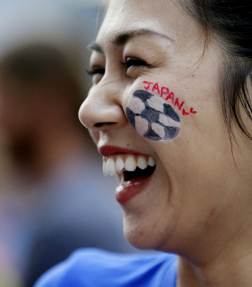 Risa Suzuki, of Japan, smiles as she stands outside BC Place stadium before the FIFA Women's World Cup soccer championship between the United States and Japan later in the day, in Vancouver, British Columbia, Canada, Sunday, July 5, 2015. (AP Photo/Elaine Thompson)