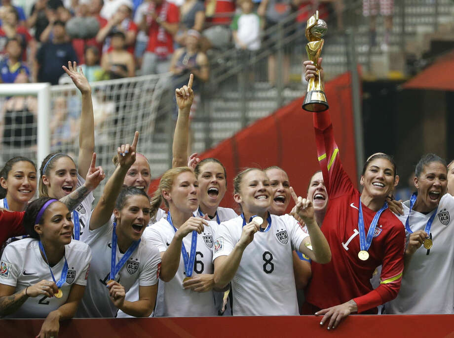ALTERNATE CROP - United States goalkeeper Hope Solo, second from right, holds up the trophy as she celebrates with teammates after the U.S. beat Japan 5-2 in the FIFA Women's World Cup soccer championship in Vancouver, British Columbia, Canada, Sunday, July 5, 2015. (AP Photo/Elaine Thompson)