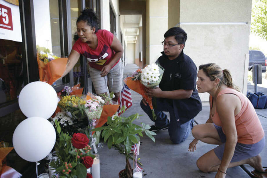 From left, Sandra Flores, Jonathan Solano and Leticia Trejo place flowers in front of a CiCi's Pizza Monday, June 9, 2014 in Las Vegas. People have begun to create a makeshift memorial in front of the restaurant where two Las Vegas Metropolitan Police officers were killed. (AP Photo/John Locher)