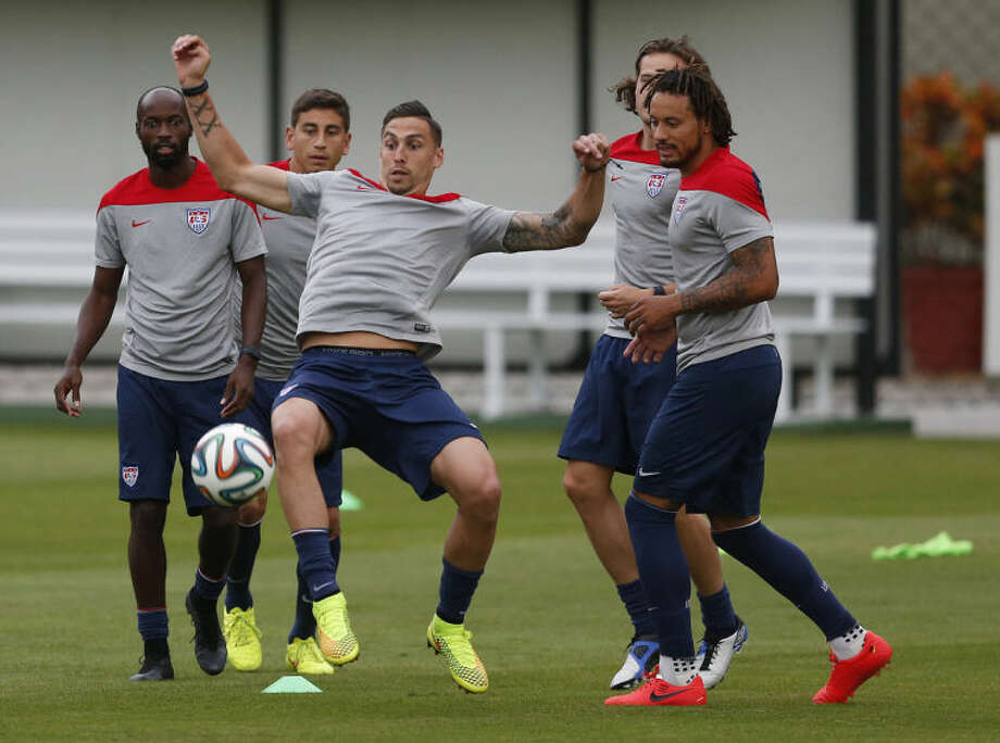 United States' Geoff Cameron attempts to keep a ball in the air as teammates look on during a training session at the Sao Paulo FC training center in Sao Paulo, Brazil, Monday, June 9, 2014. The U.S. will play in group G of the 2014 soccer World Cup. (AP Photo/Julio Cortez)