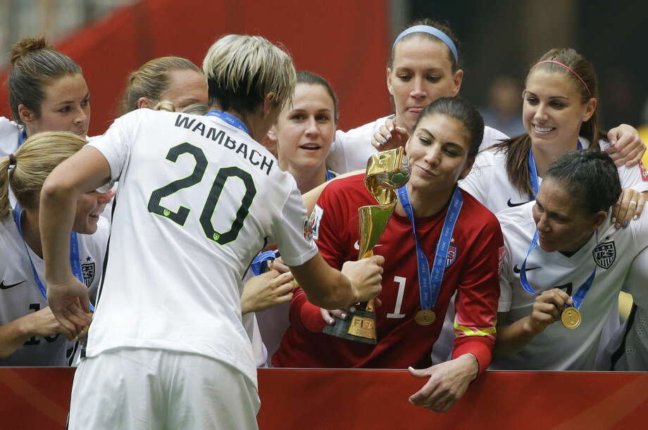 United States' Abby Wambach (20) hands the trophy to goalkeeper Hope Solo, center, after the U.S. beat Japan 5-2 in the FIFA Women's World Cup soccer championship in Vancouver, British Columbia, Canada, Sunday, July 5, 2015. (AP Photo/Elaine Thompson)