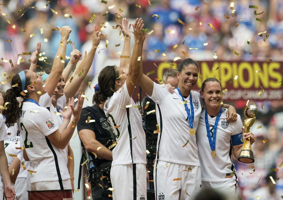 USA teammates Shannon Boxx, second from right, and Christie Rampone, far right, pose with the trophy as the USA team celebrates following their win over Japan at the FIFA Women's World Cup soccer championship in Vancouver, British Columbia, Canada, Sunday, July 5, 2015. (Jonathan Hayward/The Canadian Press via AP) MANDATORY CREDIT